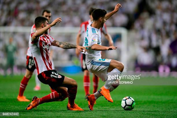 Real Madrid's Spanish midfielder Marco Asensio vies with Athletic Bilbao's Spanish defender Unai Nunez during the Spanish league football match Real...