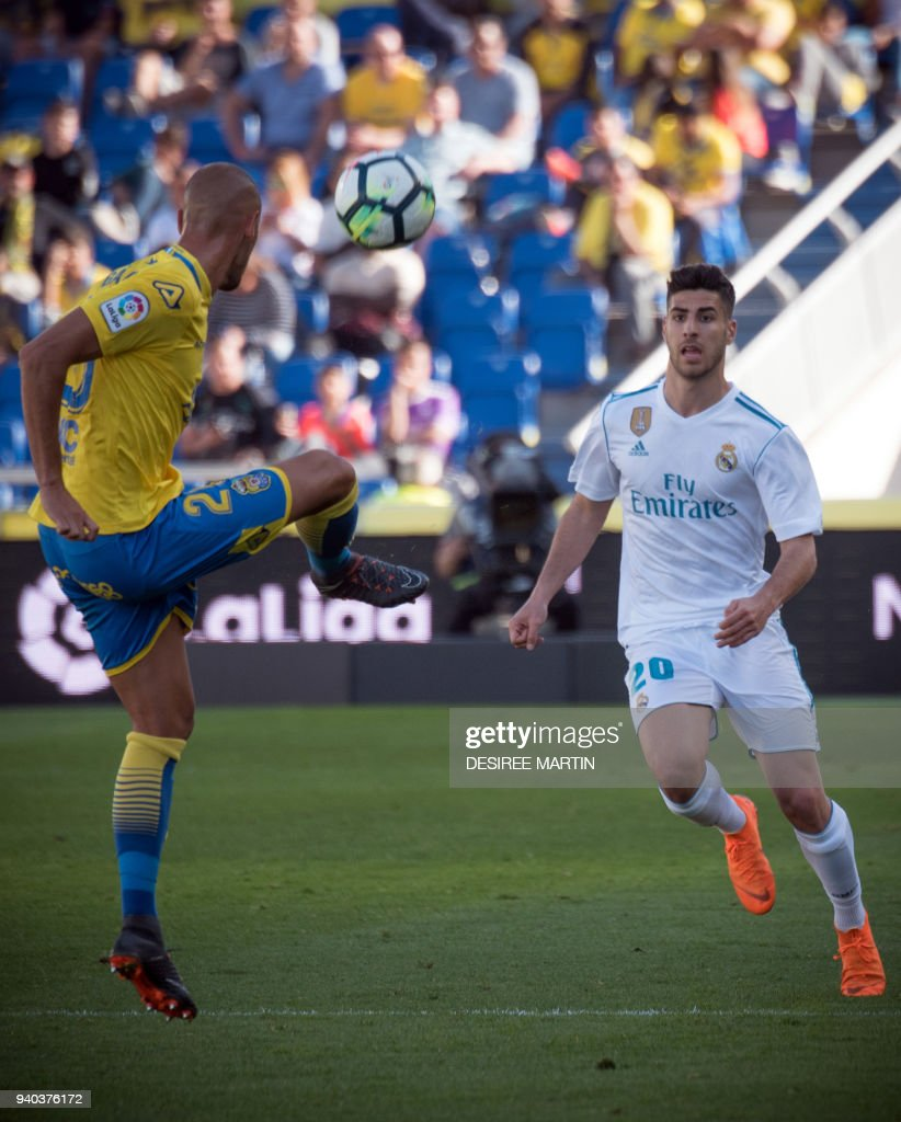 Real Madrid's Spanish midfielder Marco Asensio (R) vies with Las Palmas' defender Galvez during the Spanish League football match between UD Las Palmas and Real Madrid CF at the Gran Canaria stadium in Las Palmas on March 31, 2018. /