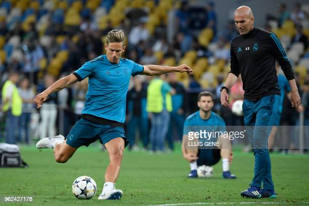 Real Madrid's Spanish miedfieder Marcos Llorente kicks the ball next to Real Madrid's French coach Zinedine Zidane during a team's training session...