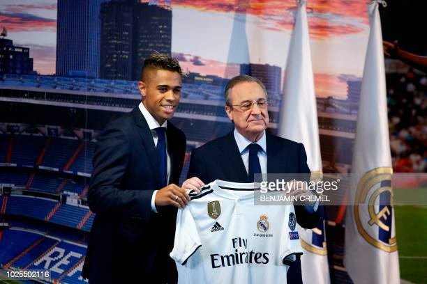 Real Madrid's Spanish-Dominican forward Mariano poses with his new jersey next to Real Madrid president Florentino Perez during his official...