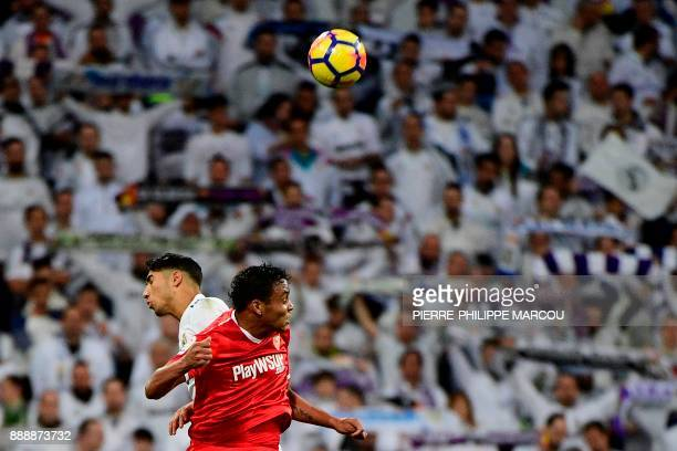 Real Madrid's SpanishMoroccan defender Achraf Hakimi heads the ball with Sevilla's Colombian forward Luis Muriel during the Spanish league football...