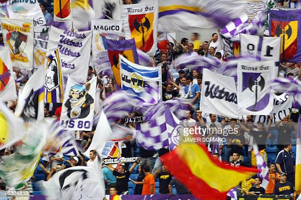 Real Madrid's supporters wave flags to cheer up their team during their Spanish league football match against Atletico Madrid at Santiago Bernabeu...