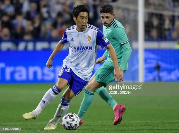 Real Madrid's Uruguayan midfielder Federico Valverde challenges Zaragoza´s Japanese midfielder Shinji Kagawa during the the Copa del Rey football...