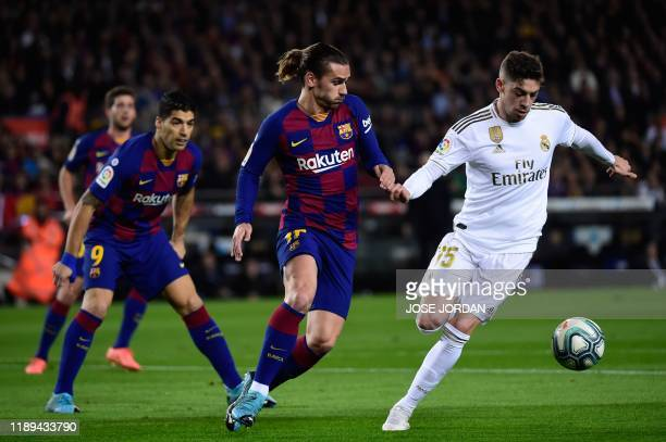 Real Madrid's Uruguayan midfielder Federico Valverde vies with Barcelona's French forward Antoine Griezmann during the El Clasico Spanish League...