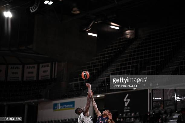 Real Madrid's US forward Trey Thompkins challenges for the ball ASVEL's French centre Moustapha Fall during the Euroleague basketball match between...