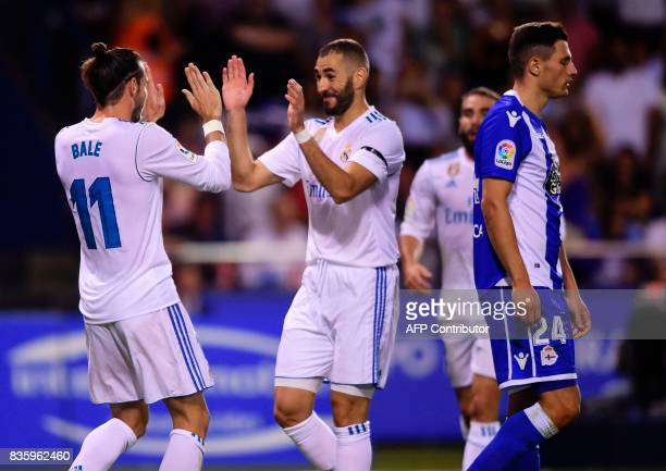 Real Madrid's Welsh forward Gareth Bale celebrates with teammate French forward Karim Benzema after scoring a goal during the Spanish league footbal...