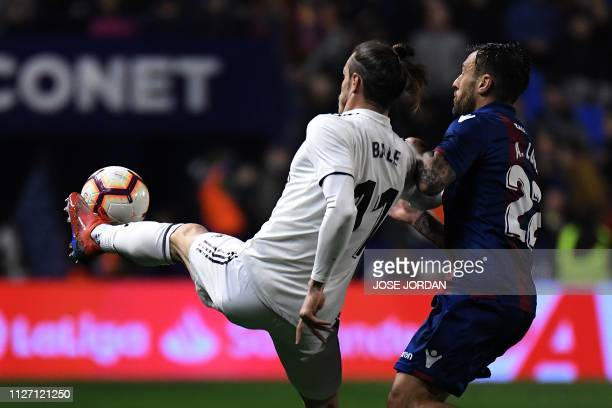 Real Madrid's Welsh forward Gareth Bale challenges Levante's Spanish defender Antonio Luna during the Spanish league football match between Levante...