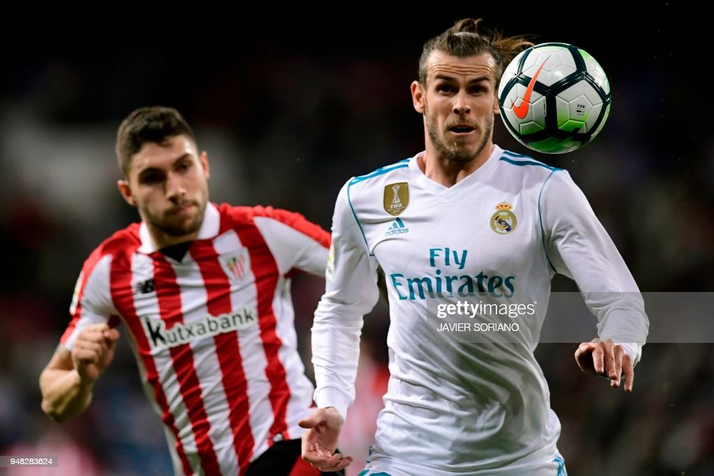 Real Madrid's Welsh forward Gareth Bale (R) eyes the ball next to Athletic Bilbao's Spanish defender Unai Nunez during the Spanish league football match Real Madrid CF against Athletic Club Bilbao at the Santiago Bernabeu stadium in adrid on April 18, 2018. /