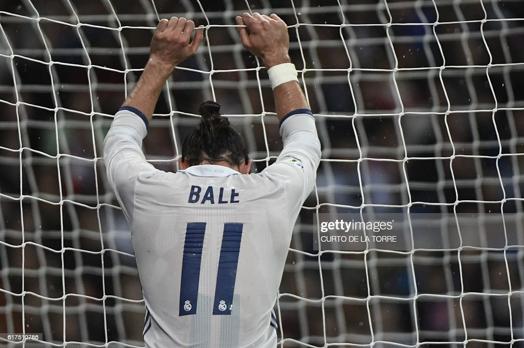 TOPSHOT - Real Madrid's Welsh forward Gareth Bale grabs the goal's net during the Spanish league football match between Real Madrid CF and Athletic Club Bilbao at the Santiago Bernabeu stadium in Madrid on October 23, 2016. / AFP / CURTO
