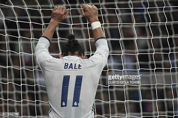 TOPSHOT Real Madrid's Welsh forward Gareth Bale grabs the goal's net during the Spanish league football match between Real Madrid CF and Athletic...