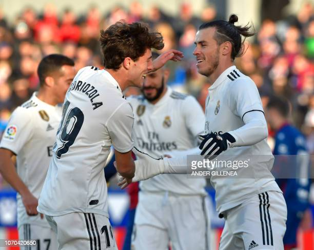 Real Madrid's Welsh forward Gareth Bale is congratulated by teammate defender Alvaro Odriozola after scoring his team's first goal during the Spanish...