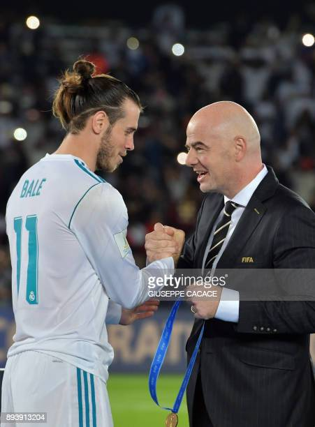 Real Madrid's Welsh forward Gareth Bale is presented a gold medal by FIFA President Gianni Infantino following the Club World Cup final football...