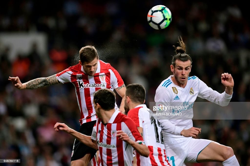 Real Madrid's Welsh forward Gareth Bale (R) jumps for the ball with Athletic Bilbao's Spanish defender Inigo Martinez during the Spanish league football match Real Madrid CF against Athletic Club Bilbao at the Santiago Bernabeu stadium in adrid on April 18, 2018. /
