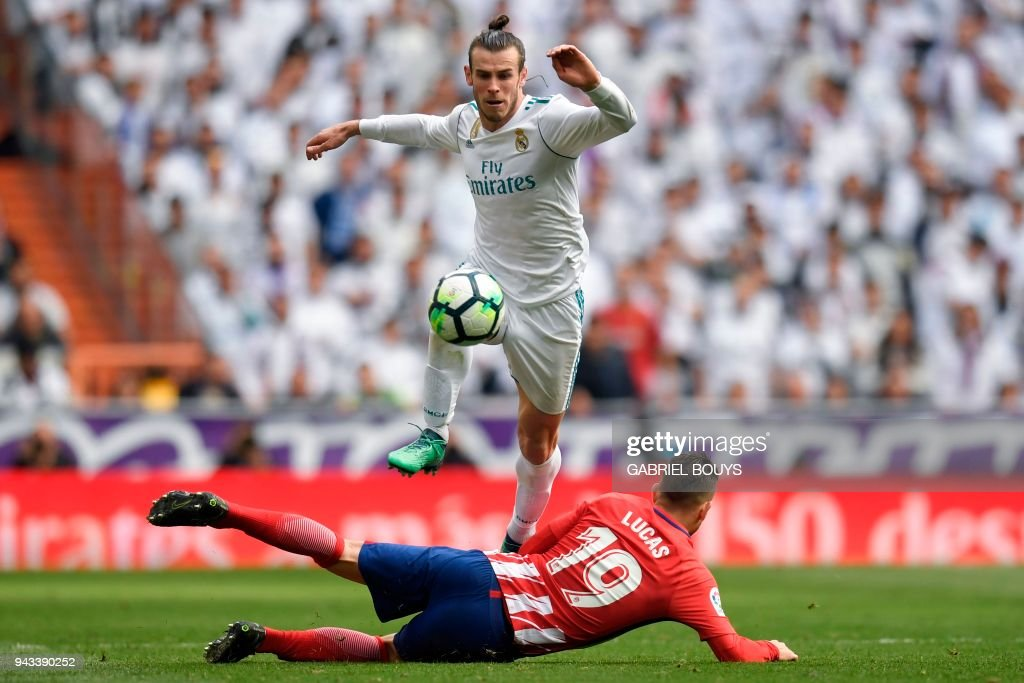 TOPSHOT - Real Madrid's Welsh forward Gareth Bale jumps over Atletico Madrid's French defender Lucas Hernandez (bottom) during the Spanish league football match between Real Madrid CF and Club Atletico de Madrid at the Santiago Bernabeu stadium in Madrid on April 8, 2018. /