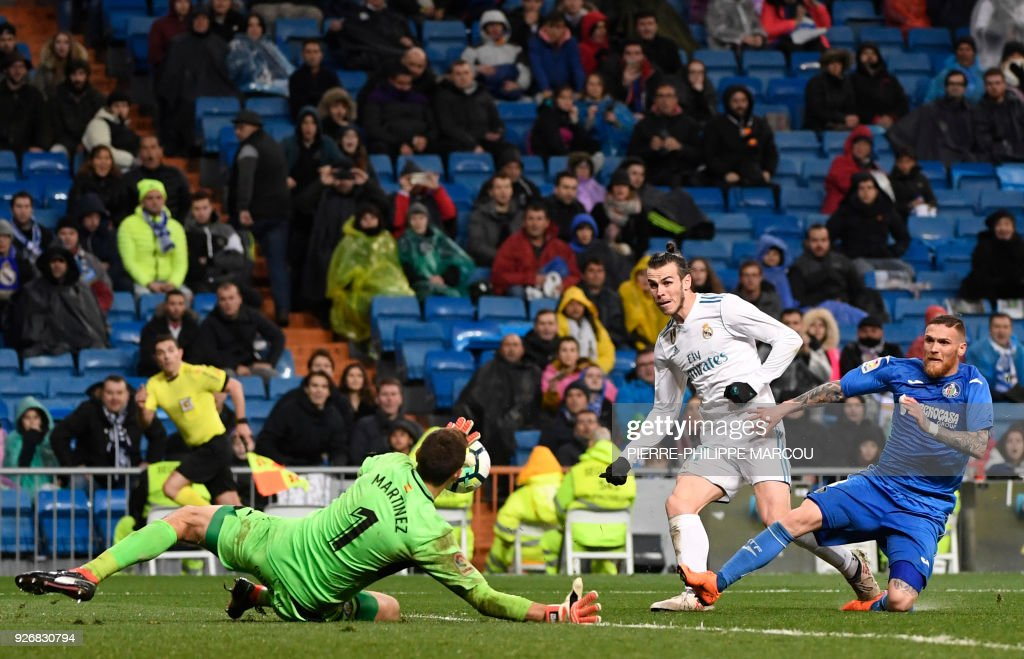Real Madrid's Welsh forward Gareth Bale (C) shoots against Getafe's Argentinian goalkeeper Emiliano Martinez (L) beside Getafe's Portuguese defender Vitorino Antunes during the Spanish league football match Real Madrid CF against Getafe CF at the Santiago Bernabeu stadium in Madrid on March 3, 2018. /