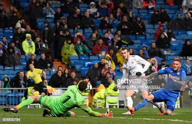 Real Madrid's Welsh forward Gareth Bale shoots against Getafe's Argentinian goalkeeper Emiliano Martinez beside Getafe's Portuguese defender Vitorino...