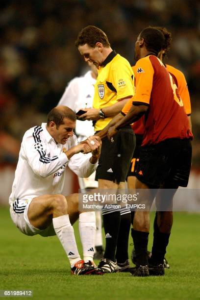 Real Madrid's Zinedine Zidane is helped up by AS Roma's Aldair as referee Hugh Dallas prepares to book him