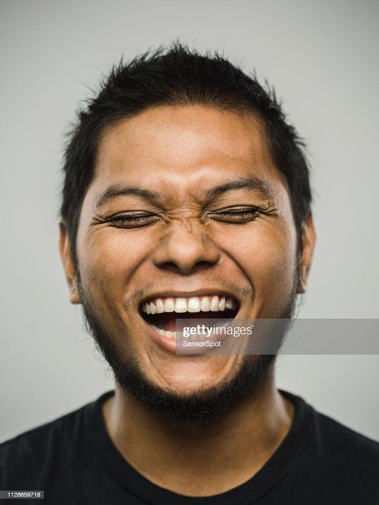 非常に興奮するいると目を閉じて実際マレーシアの若い男 : ストックフォト