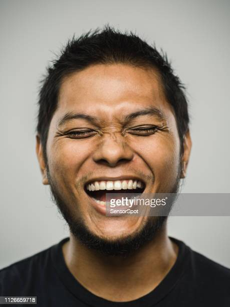 real malaysian young man with very excited expression and eyes closed - insanity stock pictures, royalty-free photos & images