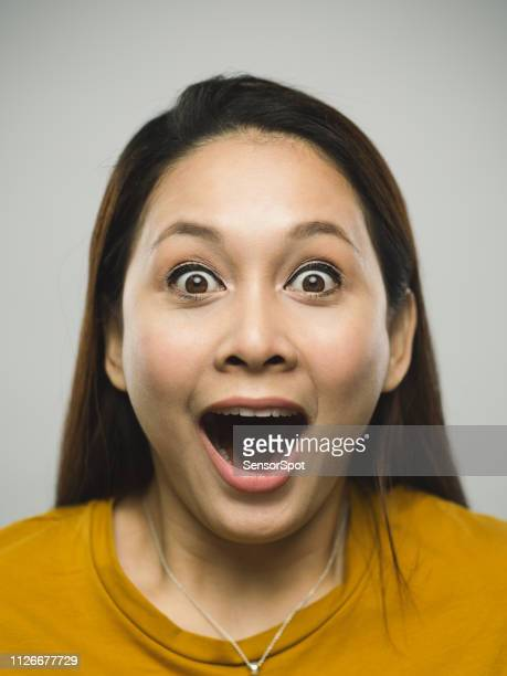 real malaysian young woman with surprised expression - impressionante foto e immagini stock