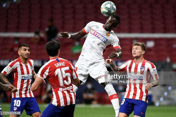 Real Mallorca's Ivorian forward Lago Junior heads the ball between Atletico Madrid's Argentine forward Angel Correa , Atletico Madrid's Montenegrin...