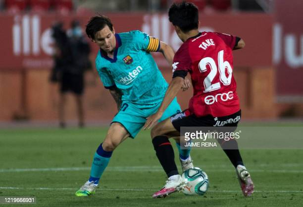 Real Mallorca's Japanese midfielder Takefusa Kubo challenges Barcelona's Argentine forward Lionel Messi during the Spanish League football match...