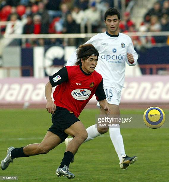 Real Mallorca's Japanese striker Yoshito Okubo runs for the ball with Getafe's Raul Albiol during their Spanish League football match at Son Moix...