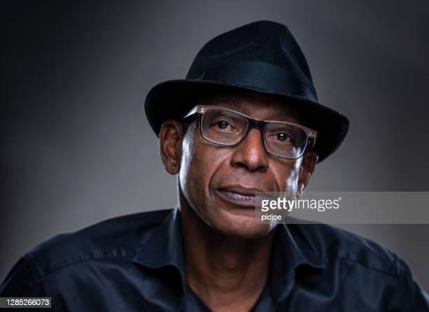 homem de verdade com uma expressão séria. retrato de um homem de verdade com chapéu preto em um fundo cinza. - só homens de idade mediana - fotografias e filmes do acervo