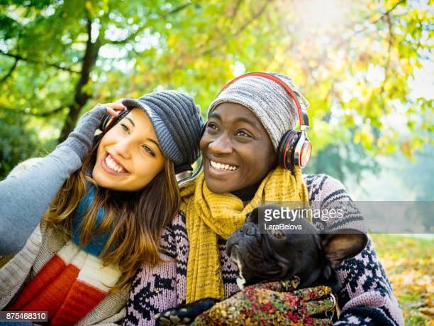 Echte Multi ethnischen Freundinnen im Park mit Hund