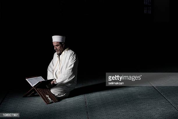 Real Muslim Imam Reading Koran On Lectern In Mosque
