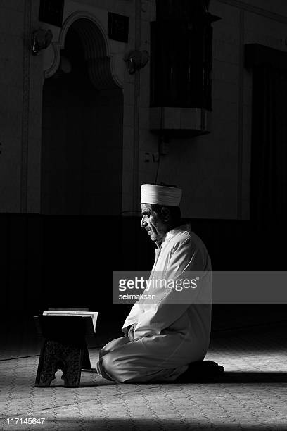 real muslim imam reading koran on lectern in mosque - praying stock pictures, royalty-free photos & images