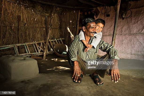 real people from rural india: happy father and son - indian slums stock pictures, royalty-free photos & images