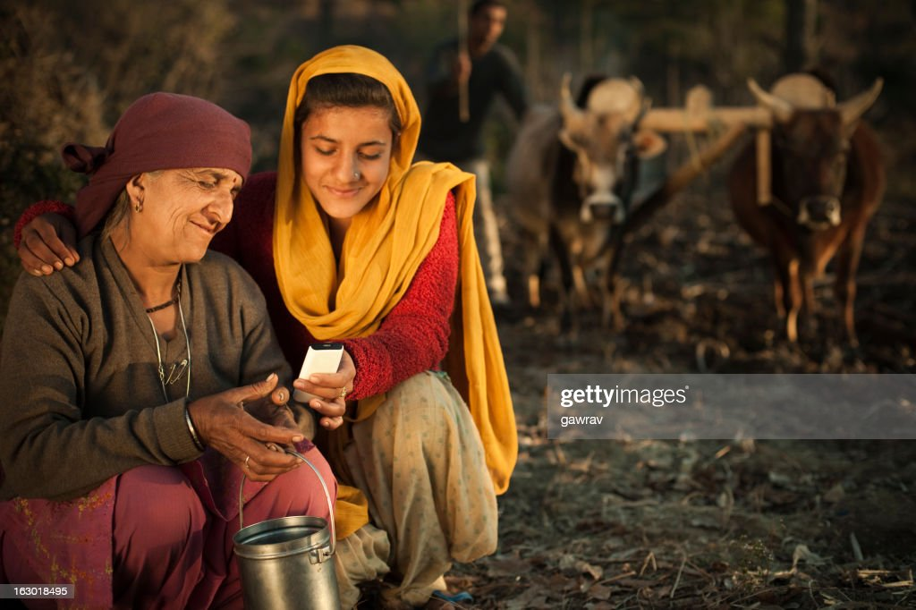 Real people from rural India: Peasant family using mobile phone : Stock Photo