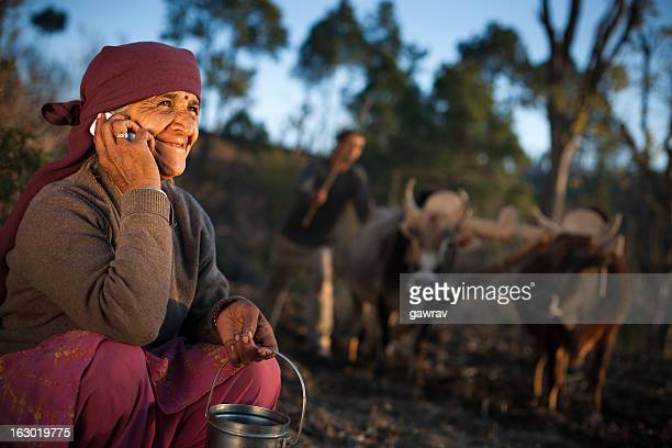 Real people from rural India: Senior peasant woman using phone