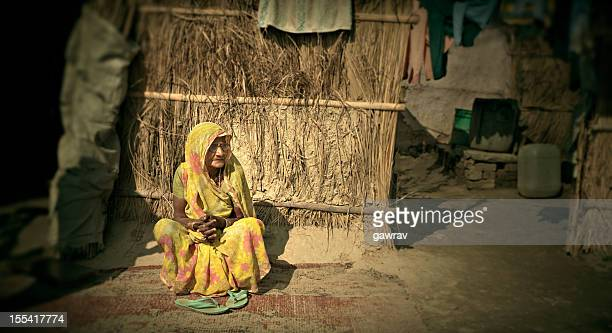 real people from rural india: senior women sitting outside hut - indian slums stock pictures, royalty-free photos & images