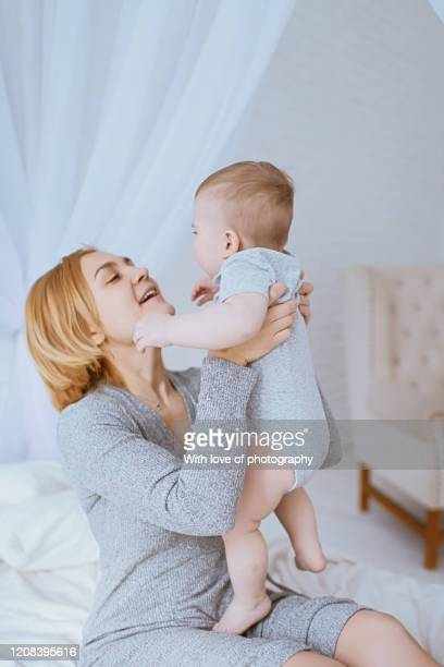 real people, mother cuddling with her baby son under 1 year, baby boy, single mother, mother's day, caucasian, beautiful motheк 30-39 years  with baby - 30 39 years stockfoto's en -beelden