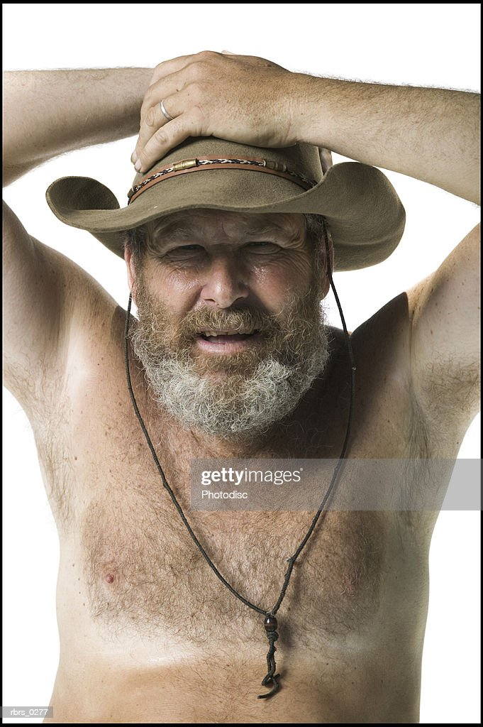 real people portrait of an adult man with no shirt and a hat as he looks at the camera : Foto de stock