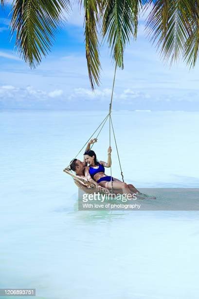 real people young adult couple on vacation, lovers in palm swing on the beach in maldives, luxury vacation, young adult man and woman on tourist resor by the ocean, island vibes, summer vacation, relaxing and embracing - love island stock pictures, royalty-free photos & images