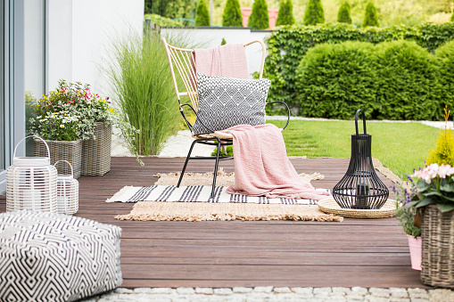 Real photo of a white pillow and pink blanket on a rattan chair standing in the garden of a luxurious house 1043486596