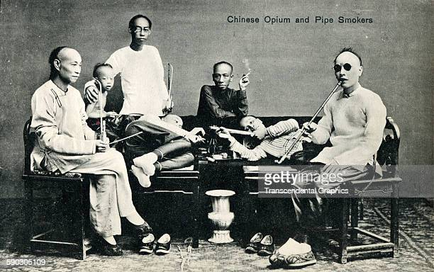 Real photo postcard features a group of opium smokers, Shanghai, China, circa 1910.