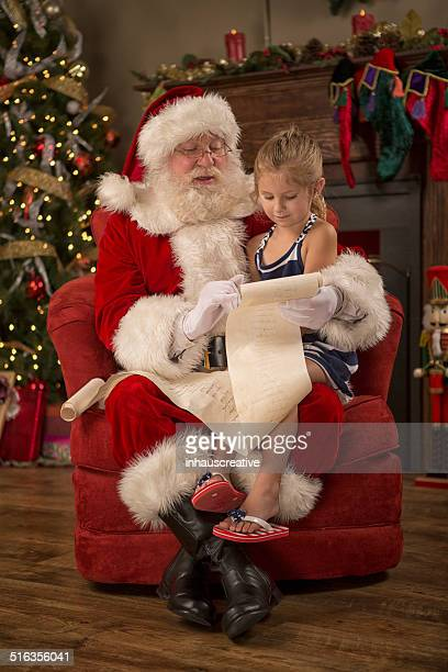 real santa claus reading naughty nice list - naughty santa stock photos and pictures