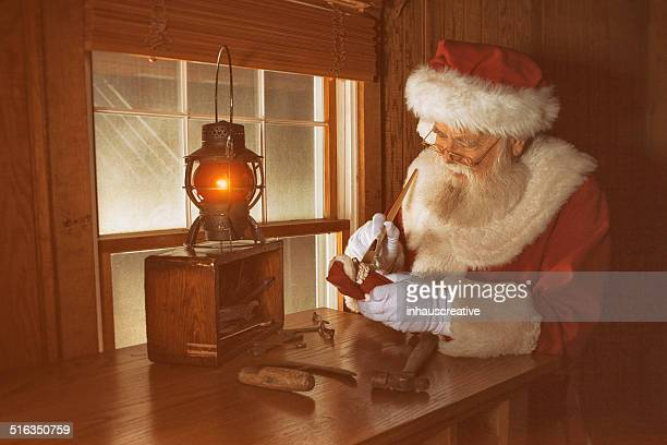 real santa claus working late night - santas workshop stock photos and pictures