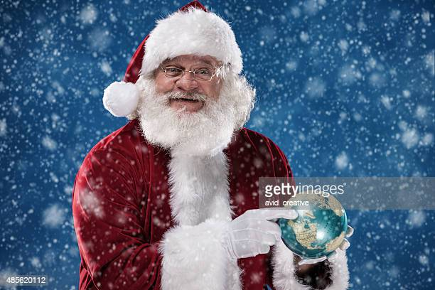 Real Santa Pointing to North Pole on Globe