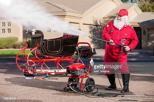 real santa washing his sleigh - sleigh stock photos and pictures