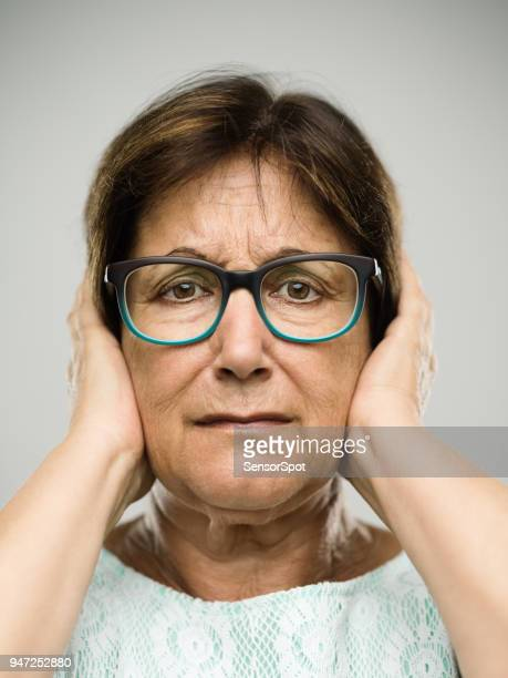 Real senior woman portrait covering ears