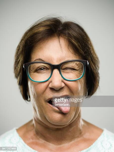 real senior woman portrait sticking the tongue out - old lady middle finger stock pictures, royalty-free photos & images