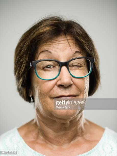 real senior woman portrait winking - fascinante imagens e fotografias de stock