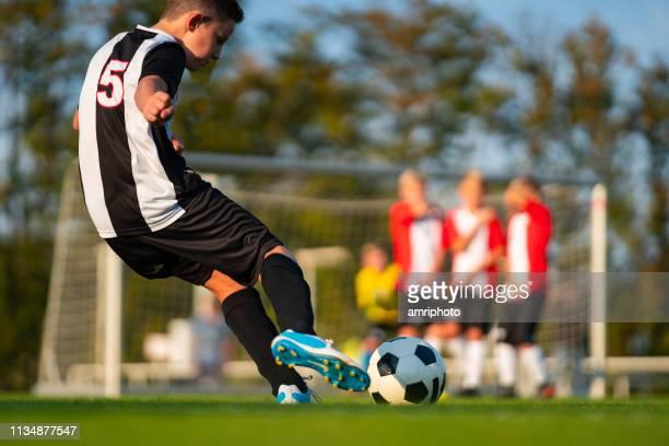 フリーキック中の本物のサッカーゲームの状況ジュニアプレーヤー - フリーキック ストックフォトと画像