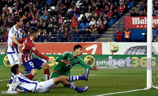 Real Sociedad's Argentinian goalkeeper Geronimo Rulli looks a ball in the net next to Atletico Madrid's Argentinian forward Luciano Vietto during the...