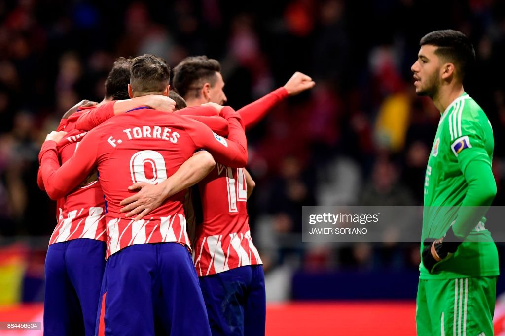 Real Sociedad's Argentinian goalkeeper Geronimo Rulli (R) reacts as Atletico Madrid's players celebrate their second goal during the Spanish league football match Club Atletico de Madrid vs Real Sociedad at the Wanda Metropolitano stadium in Madrid on December 2, 2017. /